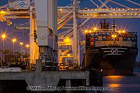 Cranes work at night on freighter berthed at port. Oakland, CA