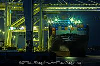 Cranes lift freight at night from ship at port. Oakland, CA