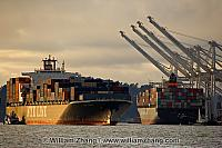 Container ship and tug pass another in port. Oakland, CA