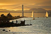 Sailboats and Bay Bridge at entrance to port. Oakland, CA